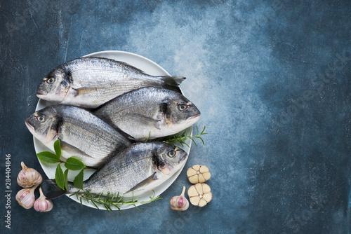 Photo Four Fresh Royal Dorades on a dish on blue backdrop