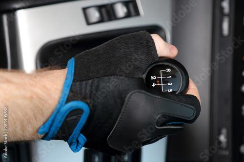 Fototapeta Dłoń w rękawiczce na dźwigni zmiany biegów w samochodzie osobowym, pięcio biegowym. obraz