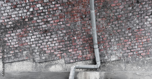 A drainpipe for rain in front of a brick wall Canvas-taulu