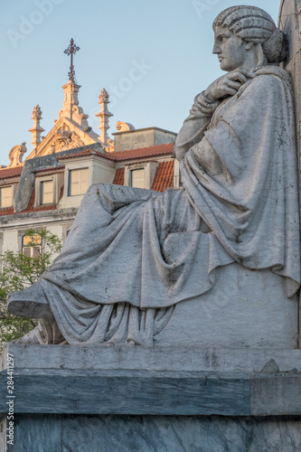 In de dag Historisch mon. Portugal, Lisbon. Church spire looms out from behind apartment buildings at sunset. Visible from Rossio square and the Pedro IV female statue figures.