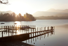 Young Couple On Pier, Sunset, Derwent Water, Lake District, Cumbria, UK