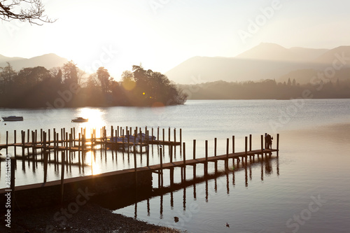 Wallpaper Mural Young couple on pier, sunset, Derwent Water, Lake District, Cumbria, UK