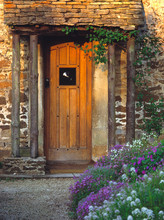 England, Chippenham. An Old Wooden Door Welcomes Visitors To A Thatched-roofed Cottage In Chippenham, Wiltshire, England.