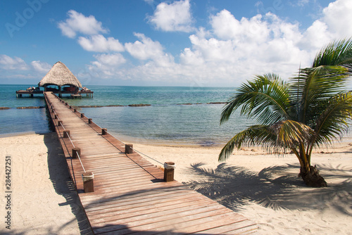 Foto auf Gartenposter Strand Placencia, Belize. Roberts Grove Resort, Pier leads from sand beach to thatch roof dock used as entertainment bar at night.
