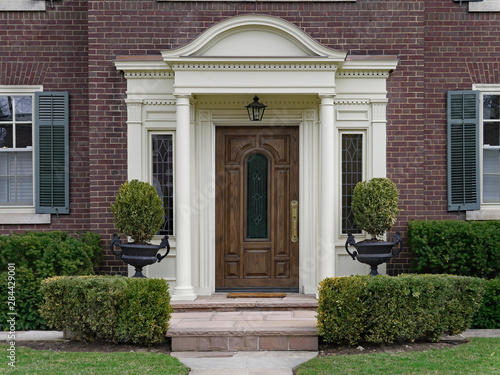 Fototapeta elegant wooden front door with portico and shrubbery