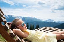 Little Girl Relaxing In Sun Lounger
