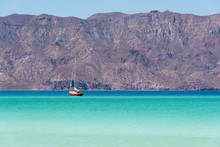 Mexico, Baja California Sur, Sea Of Cortez, Loreto Bay. Lone Sailboat On Flat Calm Water With Sierra De La Giganta Beyond