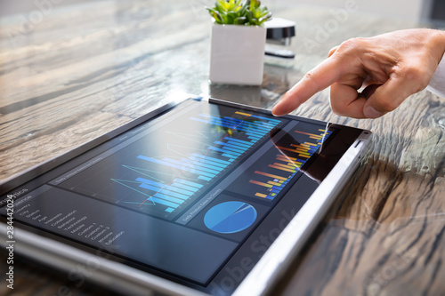 Businessman Analyzing Graph On Convertible Laptop - 284442024