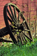 USA, Maine, Boothbay Harbor. An Old Wooden Wheel Leans Against A Red Barn Near Boothbay Harbor, Maine.