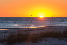US, MS, Bay St Louis. Sun Sets Gulf Of Mexico. Beach Grasses Silhouetted