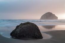 USA, Oregon. A Boulder And Sea Stack At Sunset.