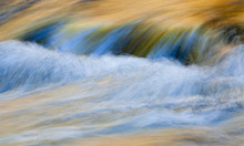Rogue River Flowing And Picking Up Reflective Colors Of Autumn