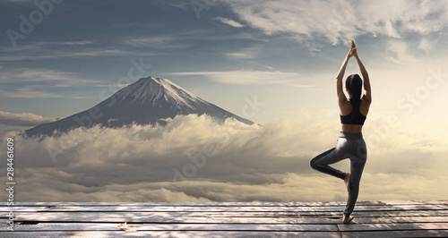 Young woman practicing yoga in the nature. female happiness. Landscape background.