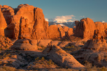 USA, Utah. Red rock formations and snow on the La Sal Mountains at sunset