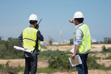 Portrait Of Two Engineer's Or Architect's Dress With Hardhat Safety Helmet And Safety Vest Have A Meeting And Pointing To New Construction Sites At Outdoor