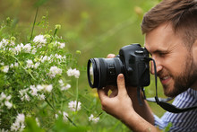 Male Photographer Taking Picture Of Beautiful Plants With Professional Camera Outdoors