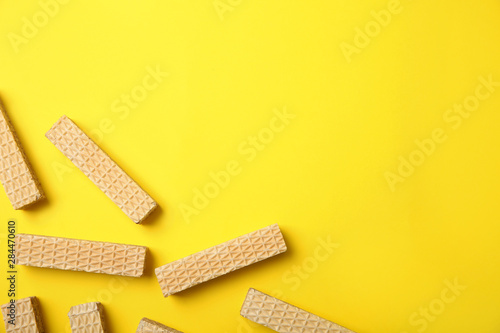 Flat lay composition with delicious crispy wafers on yellow background. Space for text