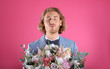 canvas print picture - Young handsome man in stylish suit with beautiful flower bouquet on pink background