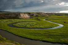 Usa, Wyoming, Yellowstone National Park. Bison In The Hayden Valley With Meandering Stream And Clouds At Sunset.