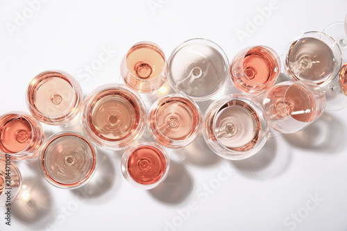 Photo  Different glasses with rose wine on white background, top view