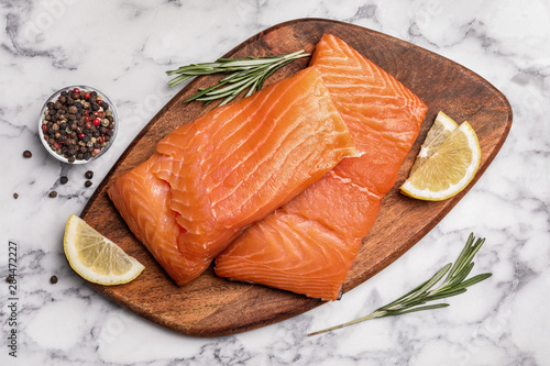 Fototapeta  Wooden board with salmon fillet on marble table, flat lay