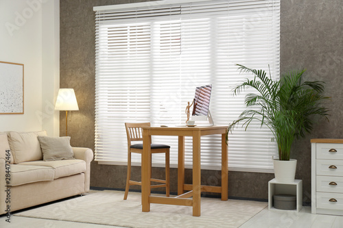 Photo Comfortable workplace near window with blinds in room