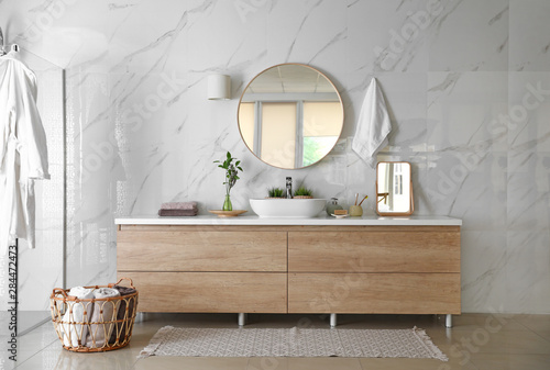 Fotografia Modern bathroom interior with stylish mirror, vessel sink and glass shower stall