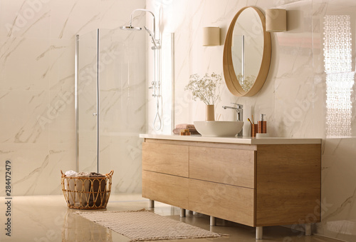 Modern bathroom interior with stylish mirror, vessel sink and glass shower stall - 284472479