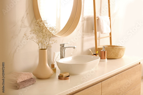Foto  Modern bathroom interior with stylish mirror and vessel sink