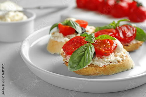 Valokuvatapetti Plate of delicious tomato bruschettas on light grey marble table, closeup