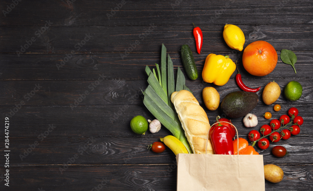 Fototapety, obrazy: Shopping paper bag with different groceries on dark wooden background, flat lay. Space for text