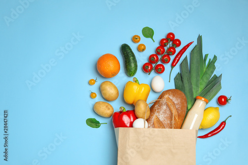 Tela Shopping paper bag with different groceries on light blue background, flat lay
