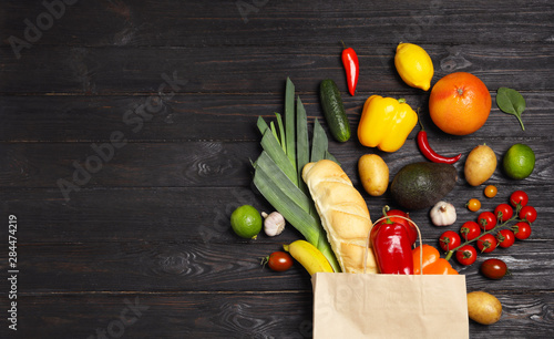 Shopping paper bag with different groceries on dark wooden background, flat lay Canvas Print