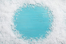 Frame Of White Snow On Light Blue Wooden Background, Top View With Space For Text. Christmas Season