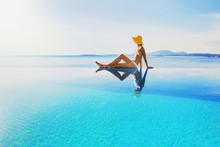 Young Woman Enjoying The Sun In The Infinity Pool. Vacations And Summer Concept