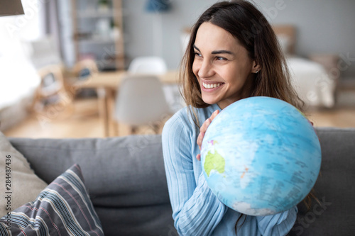 Portrait of a beautiful happy woman with a globe indoors.