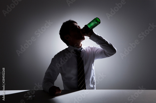 Photo Image of a businessman drinking alcohol by himself.