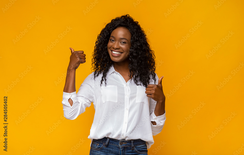 Fototapeta Happy black woman showing thumbs up at studio