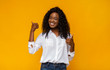 Happy black woman showing thumbs up at studio