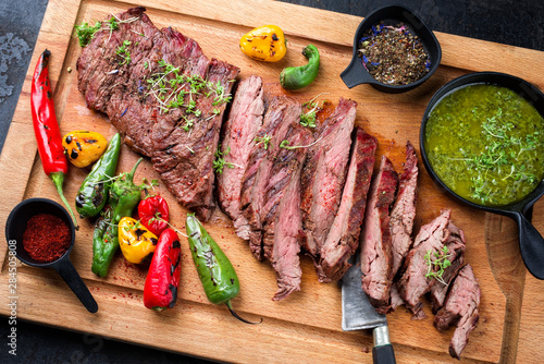 Recess Fitting Steakhouse Modern design barbecue dry aged wagyu bavette de flanchet steak with chili and chimichurri sauce as top view on a wooden cutting board
