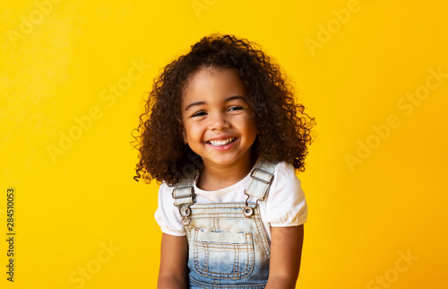 Fényképezés Happy smiling african-american child girl, yellow background