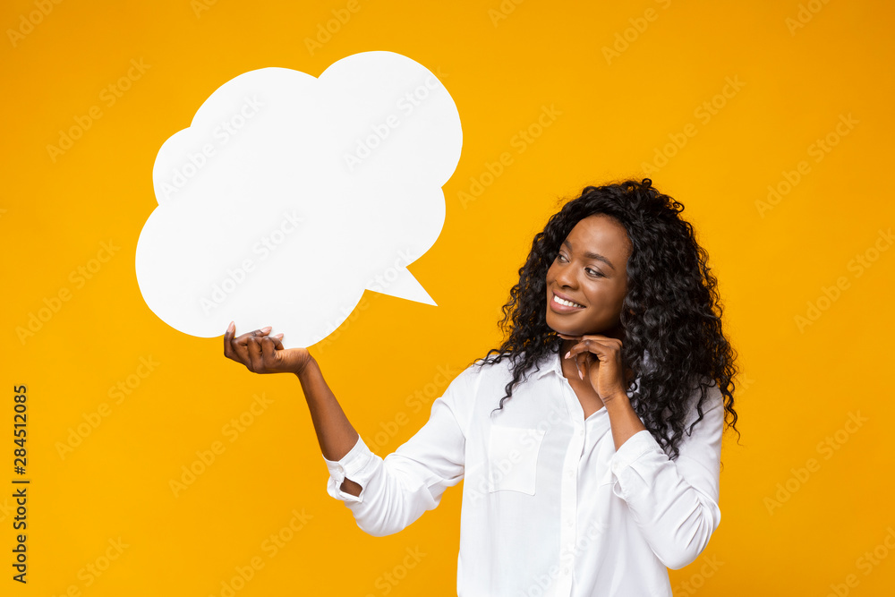 Fototapeta Playful afro girl looking at communication bubble in her hand