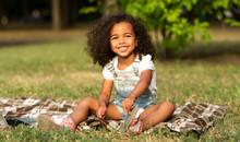 Adorable Girl Sitting On Blanket At Nature, Enjoying Summertime