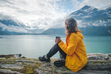 A Young Beautiful Girl Is Drinking Tea On The Shore Of The Fjord, A Trip To Norway, The Nordic Beauty