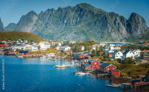 Photo sur Toile Europe du Nord View of the city of Reine on the Lofoten islands, a beautiful bright landscape, white and red houses on a background of rocks at sunset