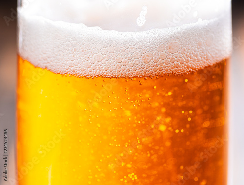 Fotografia  A close view of a glass of beer showing bubbles and foam top