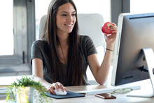 Smiling Young Business Woman Eating A Red Apple While Working With Computer In The Office.