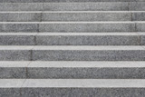 Fototapeta Na drzwi - Grey cobblestone stairs in the city, background with grunge texture