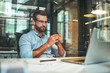 Fresh coffee. Portrait of young and successful bearded man holding cup of coffee and looking at laptop while sitting at his working place