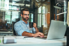 Morning Coffee. Portrait Of Young And Successful Bearded Man In Eyeglasses Holding Cup Of Coffee And Working With Laptop While Sitting At His Working Place